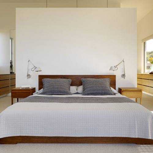 Modern minimalist master bedroom with headboard wall