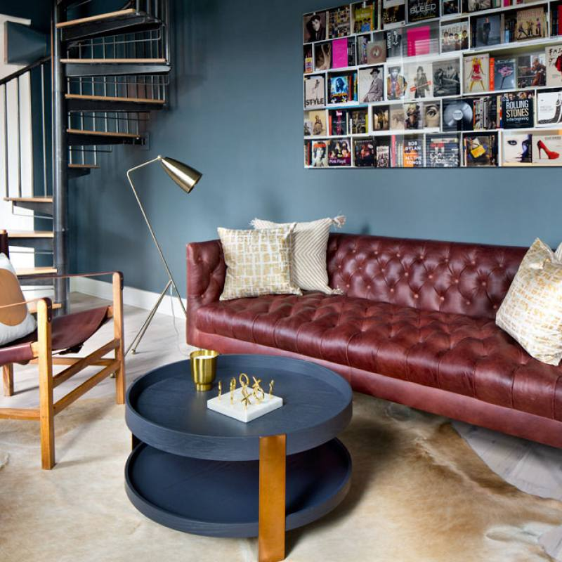 Eclectic living room with red sofa by grisoro