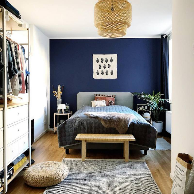 Bohemian inspired masculine bedroom with navy accent wall