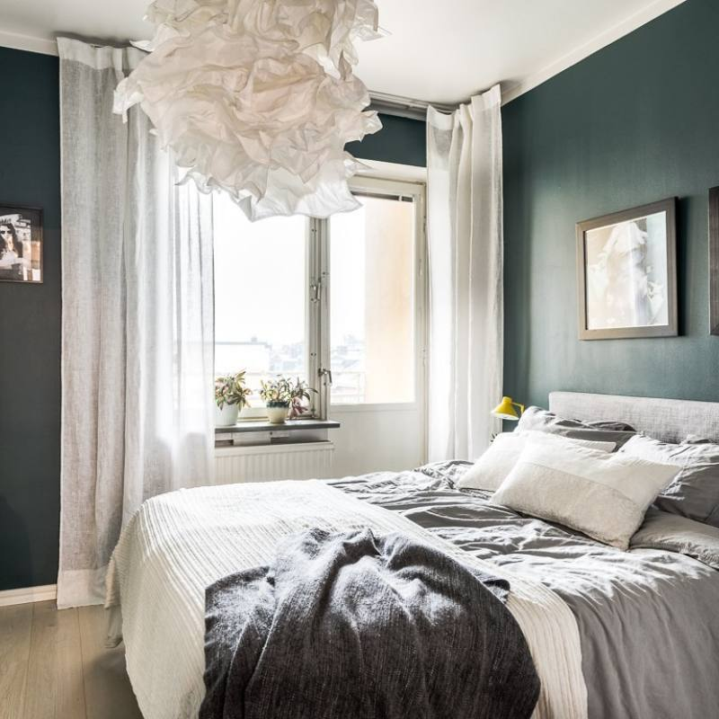 Modern nordic inspired moody bedroom with dark teal walls
