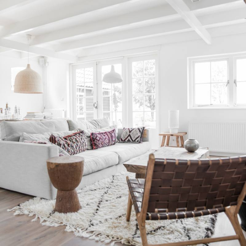 All white modern bohemian living room with morrocan rug