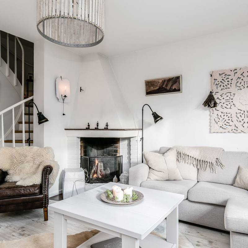 White scandi-style bohemian rustic living room with a fireplace