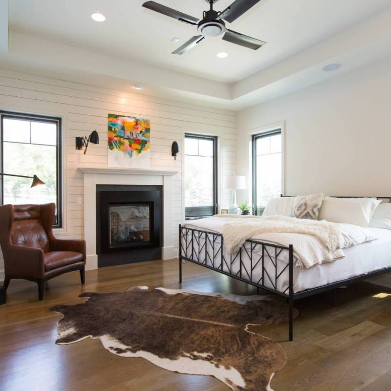 Master farmhouse style bedroom with cowhide rug