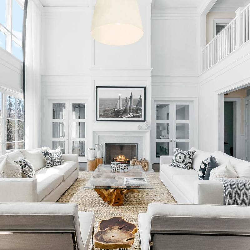 All white modern open concept living room with fireplace